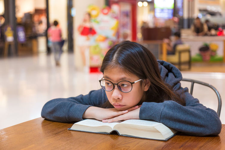 Asian teenager girl waiting alone for her family at a shopping mall, reading her book Alone Asian  Reading Waiting, Book Desk Education Eyeglasses  Female Focus On Foreground Girl Learning One Person Portrait Real People Sitting Student Table