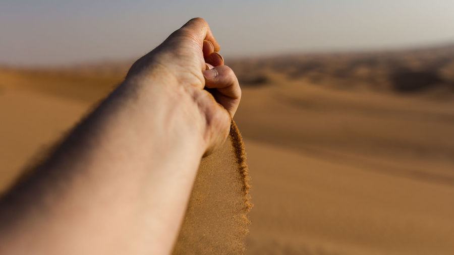 Cropped Hand Of Man Playing With Sand At Desert