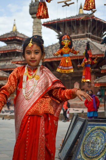 Portrait of girl in traditional clothing standing at temple