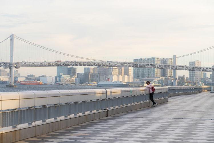 Man standing on bridge in city against sky