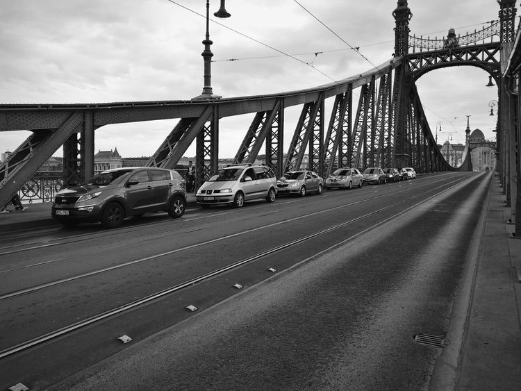 Traffic. Bridge - Man Made Structure Transportation Connection Sky Suspension Bridge Travel Destinations Travel Cable Mode Of Transport Outdoors Cloud - Sky Car Built Structure City Road Steel Day No People The Street Photographer - 2017 EyeEm Awards Monochrome Monochrome Photography Blackandwhite Blackandwhite Photography Architecture Electricity Pylon