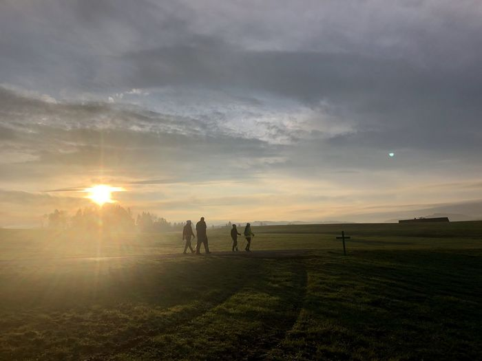 People on field against sky during sunset