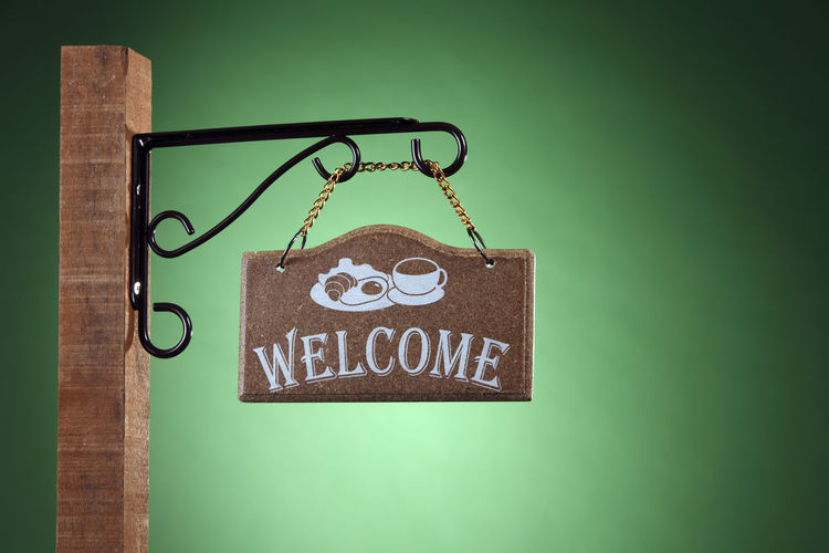 welcome signage on the green background Sign Signage Wood - Material Isolated Signboard Board Wood Hanging Blue Directional Sign Road Green Background This Way Chain Hanger Vintage Village Retro Signpost Empty Direction Textured  Message Information Panel Plaque Copy Space No People Close-up Text Welcome Communication Green Color Indoors  Art And Craft Studio Shot Still Life Colored Background