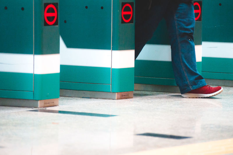 Low section of man walking by turnstile
