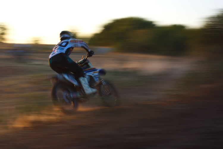 Blurred motion of man riding motorcycle on tree