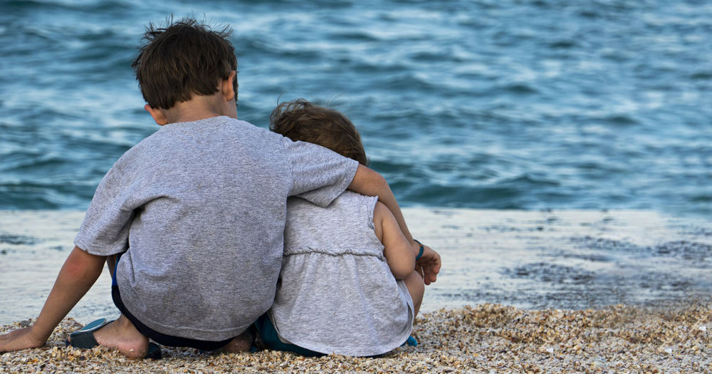 Rear view of siblings sitting at beach