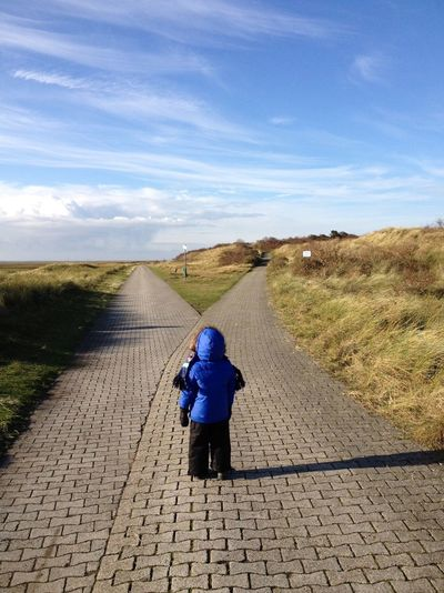 Rear View Of Boy Waring Winter Coat Standing On Footpath Against Sky