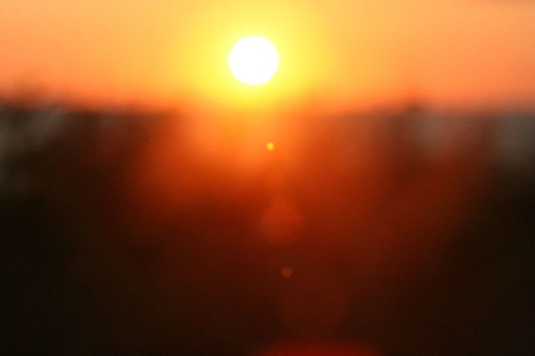 Defocused image of sun in sky during sunset
