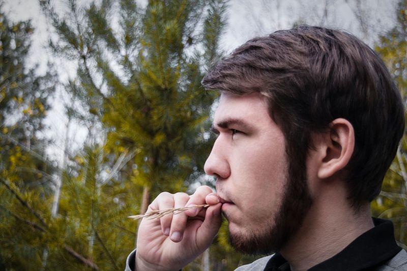 Bearded Man Imitating Of Smoking Against Trees