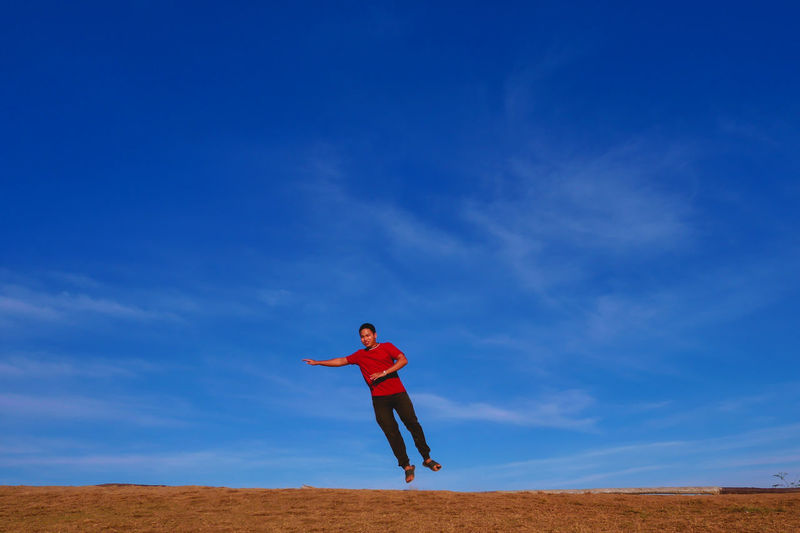 The man jumps from the floor. this scene includes dry grass and cirrus cloud.