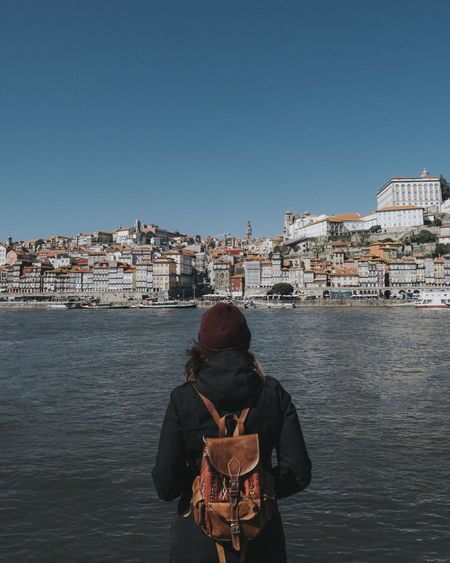 Rear view of woman standing by river against clear sky
