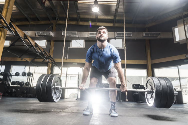 Young Man Lifting Barbells At Brightly Lit Gym