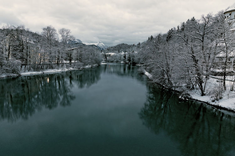 Scenic view of canal against sky during winter