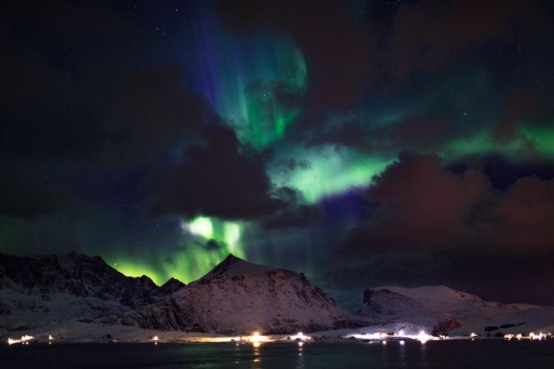 Aurora polaris over lake against sky