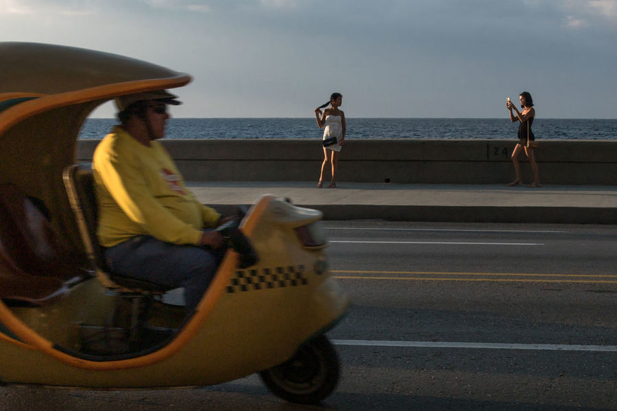 La Habana, noviembre 2016: Malecon Coco Taxi Driver Malecon Adult Adults Only Beach Day Focus On Background Full Length Horizon Over Water Leisure Activity Lifestyles Outdoors People Real People Sea Sitting Sky Street Photography Tourism Two Young Women Water Young Adult