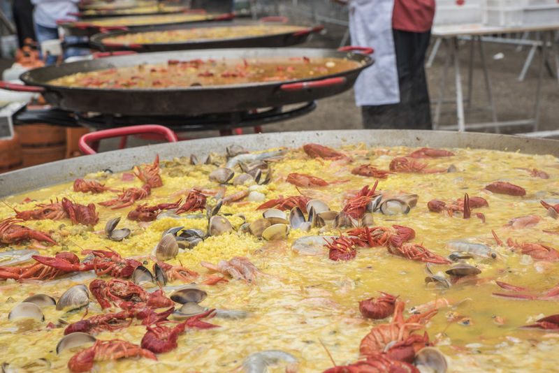Outdoor preparation of Spanish traditional food Paella Cheff Clams Clamshells Close-up Cooking Crabs Day Event Food Freshness Healthy Eating Healthy Food Market Outdoors Paella People Preparation  Preparing Food Real People Rice Saffron Seafood SPAIN Spanish Food Spice