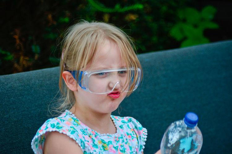 Cute girl making face while wearing protective eyewear