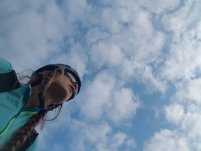 Low angle view of woman in sunglasses against sky