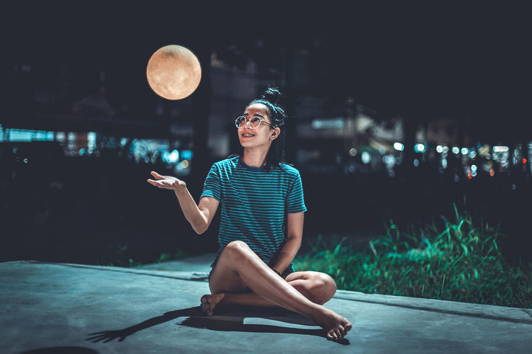 Smiling Woman Looking At Artificial Moon While Sitting On Footpath At Night