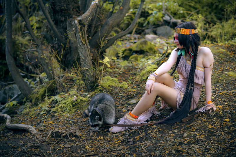 Woman With Raccoon Sitting In Forest
