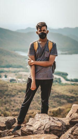 Man wearing sunglasses standing on rock