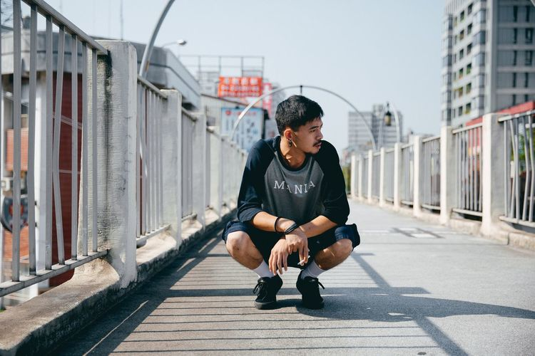 Young man sitting on wall in city against sky