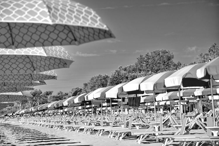 Deck chairs by parasols against sky