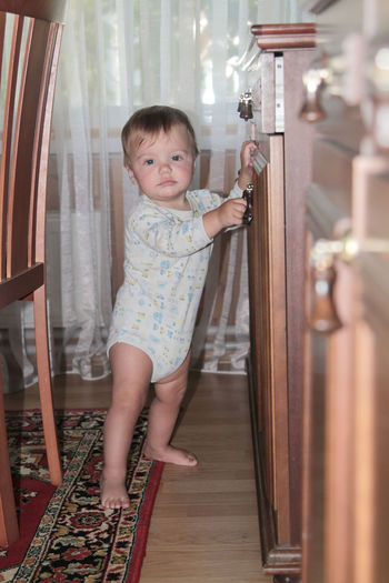 Portrait of cute baby girl standing at home