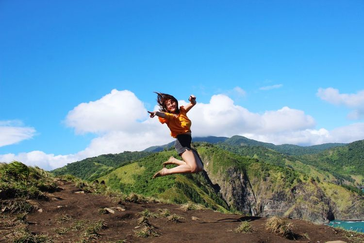 Mid adult woman jumping on mountain against blue sky during sunny day