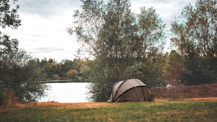 Tent on field by lake against sky