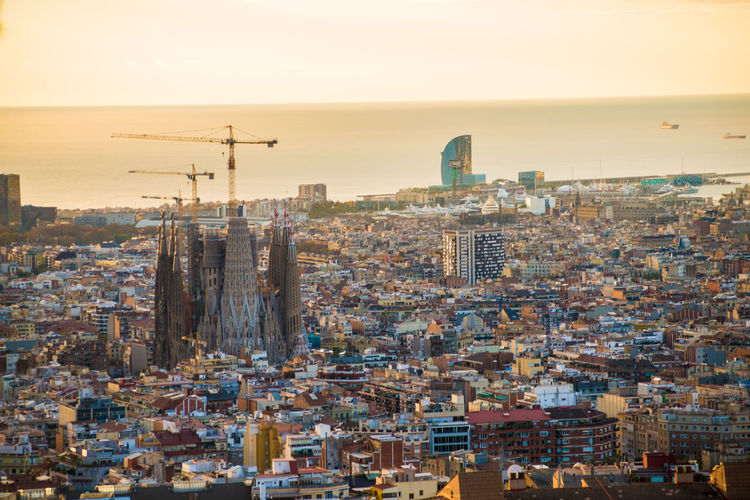 Aerial view of sagrada familia amidst buildings during sunset
