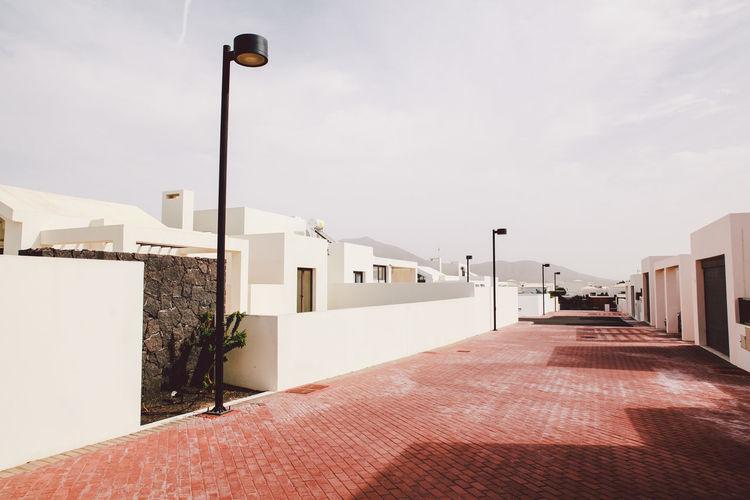 Empty Street By Buildings Against Sky In City