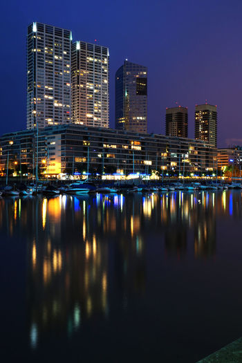 Reflection Of Colorful Lights On River In City At Night