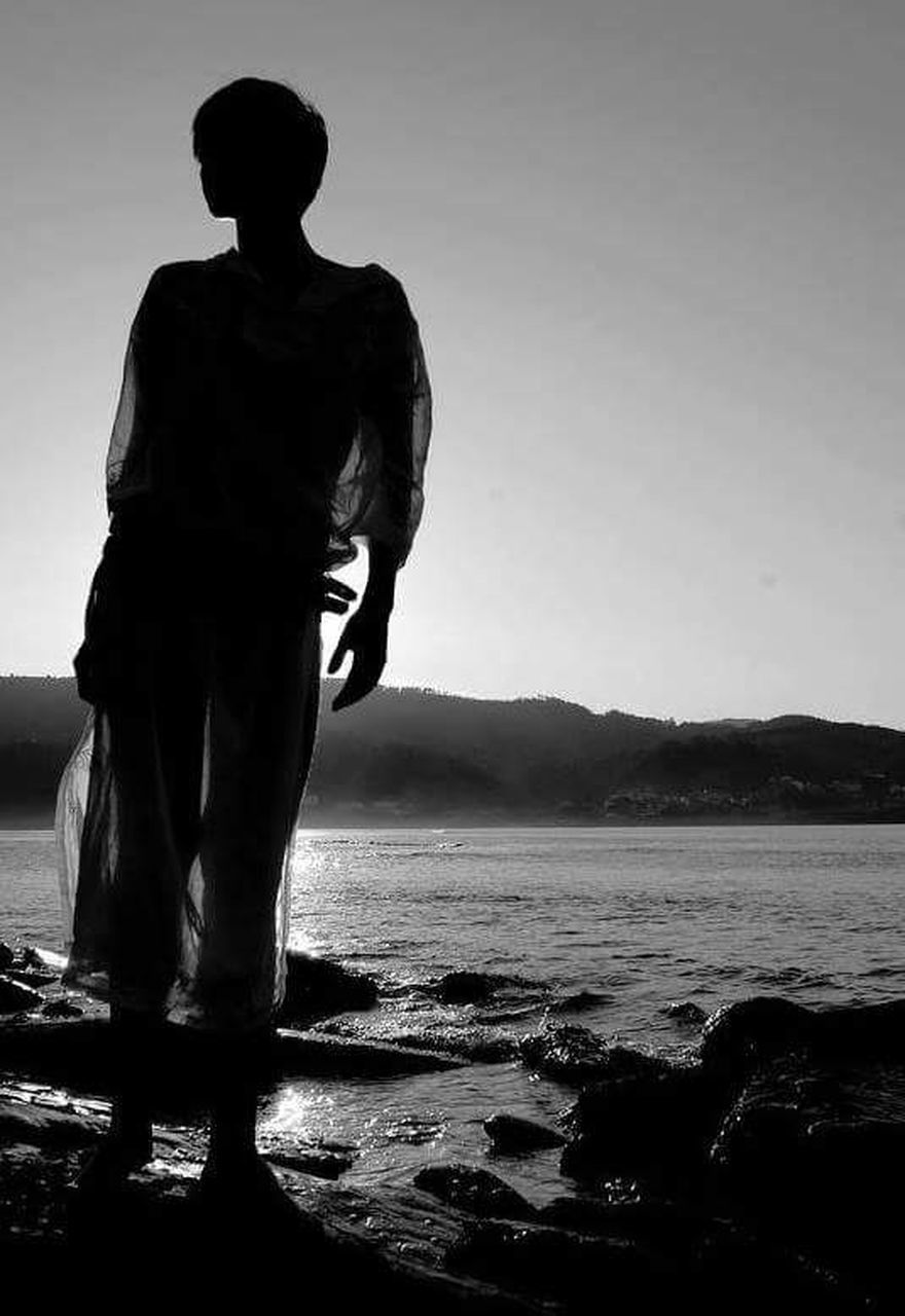 silhouette, full length, tranquil scene, one person, beach, standing, tranquility, sky, beauty in nature, water, sea, scenics, nature, outdoors, mountain, one man only, men, clear sky, real people, adult, day, only men, adults only, people, young adult