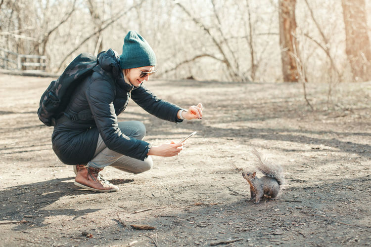 Woman taking picture of squirrel in park. tourist traveler girl snapping photos of wild animal