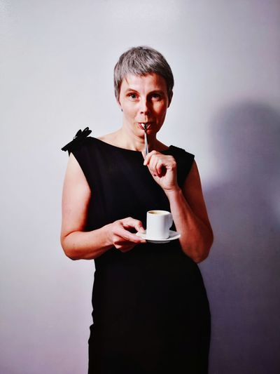 Mature Woman Holding Coffee Cup While Standing Against Wall