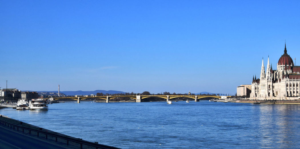 Danube river by hungarian parliament building against clear blue sky in city
