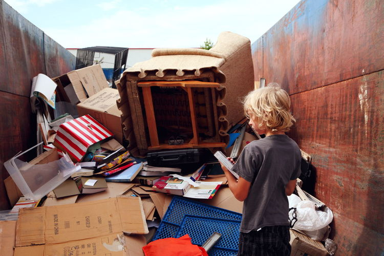 Rear view of boy standing by abandoned objects in dumpster