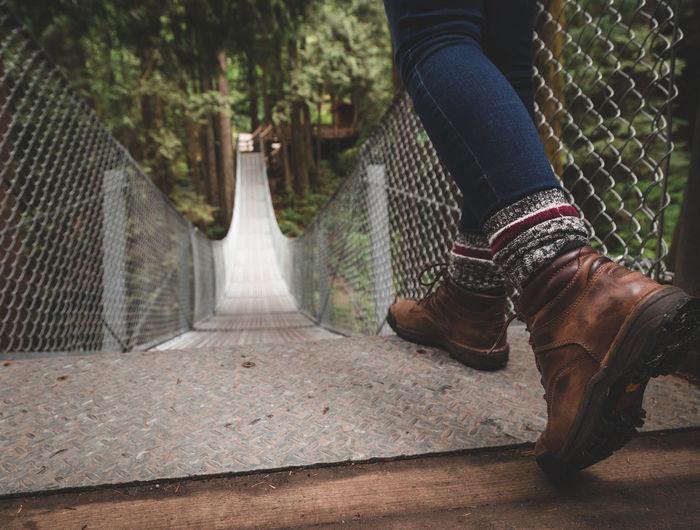 Low section of woman walking on footbridge