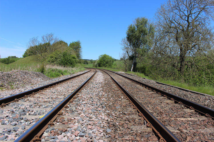 Railroad tracks in countryside against clear blue sky