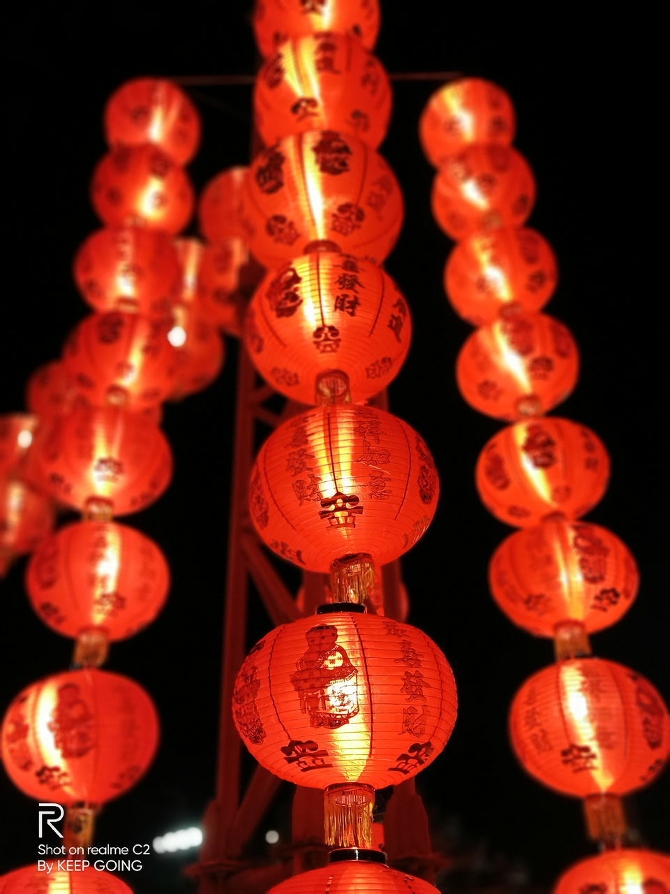 LOW ANGLE VIEW OF ILLUMINATED LANTERNS HANGING AGAINST LIGHT