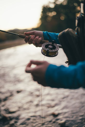 Close-up of hand holding fishing rod over sea