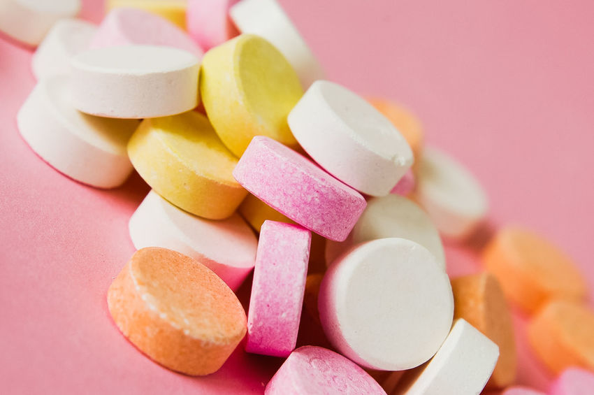 Close up of pile of chewable antacid acid indigestion relief tablets with fruit flavour in pastel colors, such as pink, yellow, orange and white on light pastel pink background Drugs Medicine Pillow Pink Relief Remedy Acid Reducer Chewables Colorful Colorfull Heartburn Medicine And Healthcare Orange Color Pastel Colors Tablets Yellow