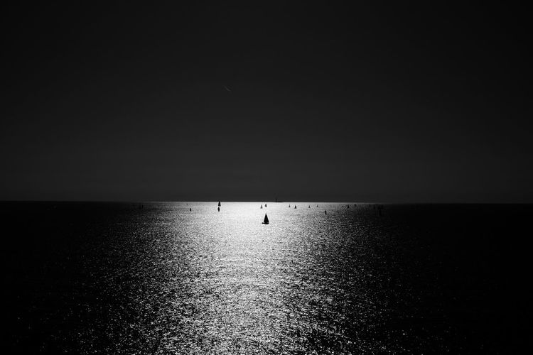 Silhouette of sailing boats in ocean against sky