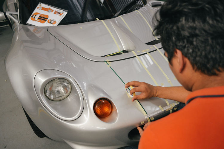 Rear view of mechanic applying adhesive tape on car