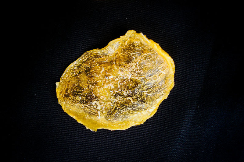 High angle view of lemon on rock against black background