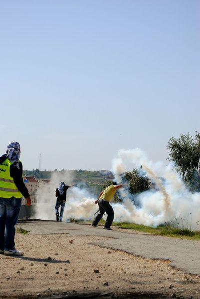 Taken with the Nikon D300. Throwing back teargas to save the rest of the us. Taking One For The Team The Teargas Tango Elégance Fightingforpeace Salam. Protest Palestine Bil'In Regal & Righteous.