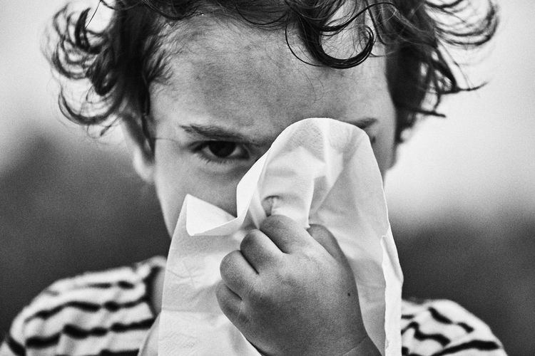 Close-up portrait of boy cleaning nose