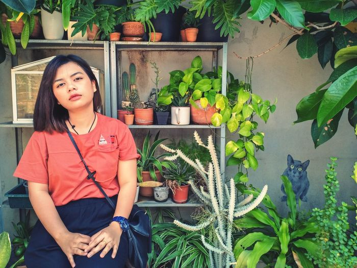 Portrait of young woman sitting against potted plants