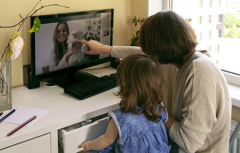 Mother with daughter video conferencing over computer at home